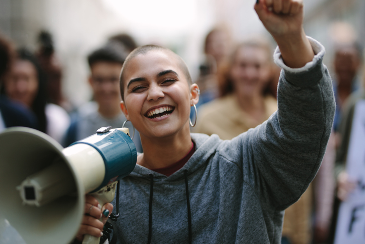 Hymyilevä nainen protestoi kadulla megafonin kanssa