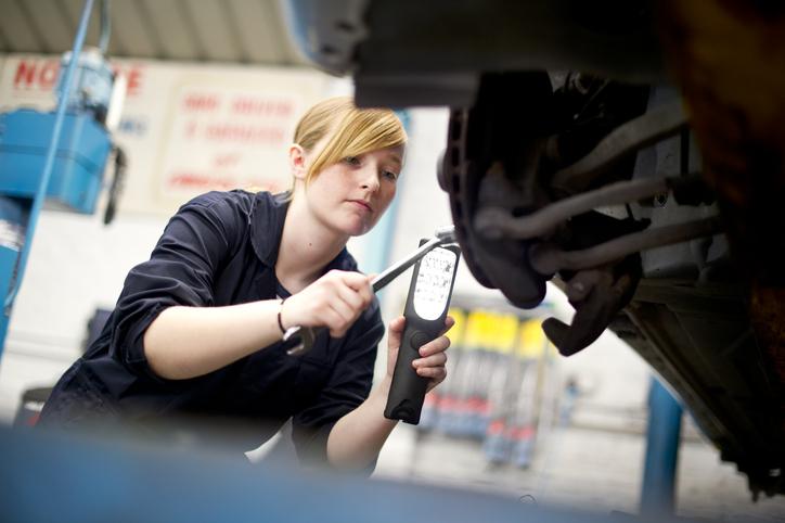 Nuori autokorjaaja-harjoittelija tekee autoon huoltoa