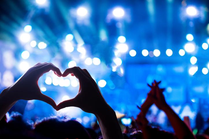 Konserttiyleisön silhuetti vasten lavan valoja, kädet ylhäällä sydämen muodossa