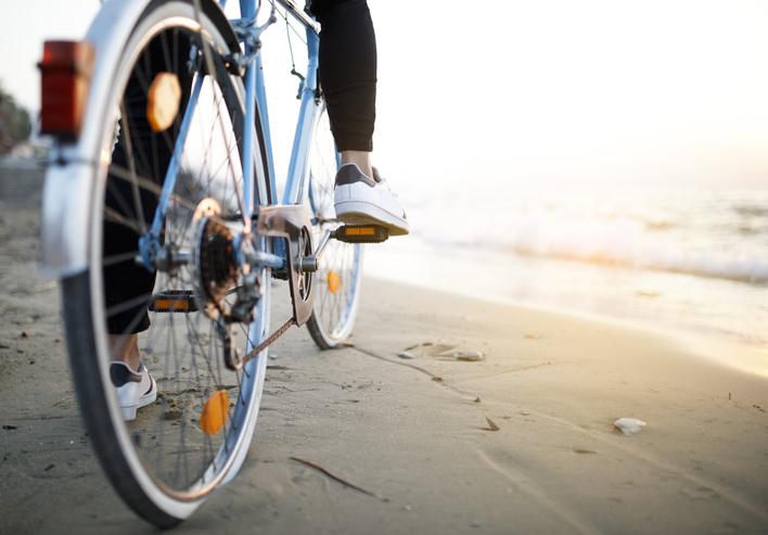 Nuori henkilö rannalla polkupyörän selässä